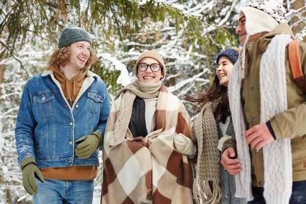Roześmiani młodzi ludzie w zimowym lesie