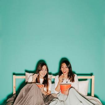 Roześmiani przyjaciele je popkorn na łóżku