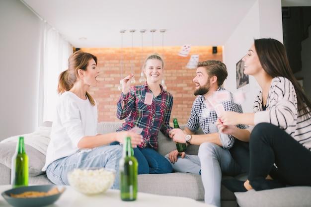 Roześmiani przyjaciele rzuca z karta do gry