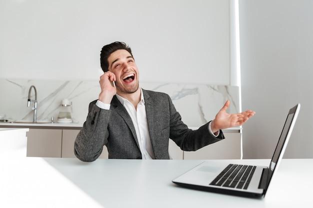 Roześmiany biznesowy mężczyzna siedzi przy stołem z laptopem