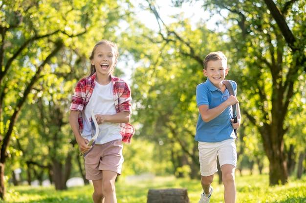 Roześmiany chłopak i dziewczyna biegnący w parku