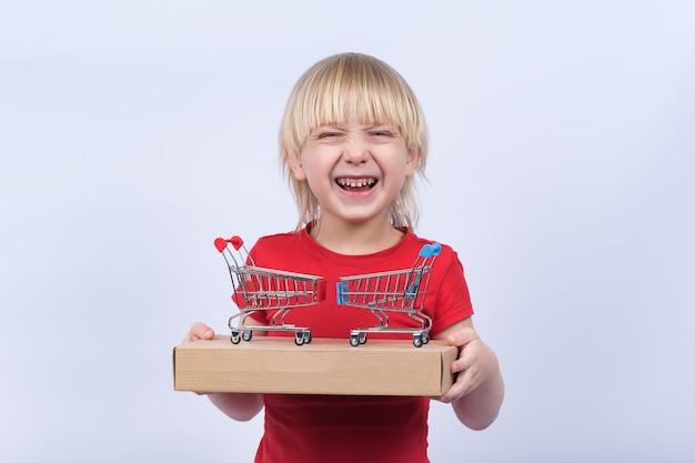 Roześmiany chłopiec trzyma paczkę i dwa wózki sklepowe. kup zabawki online koncepcji