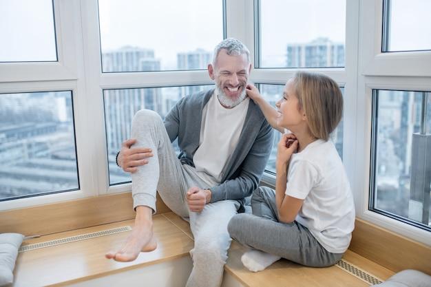 Roześmiany mężczyzna i szczęśliwa dziewczyna rozmawia.