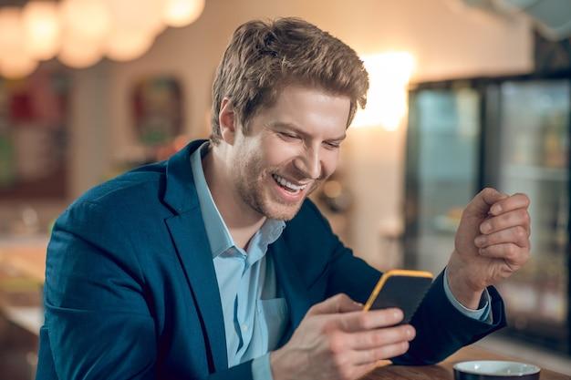 Roześmiany mężczyzna w garniturze patrzący na smartfona