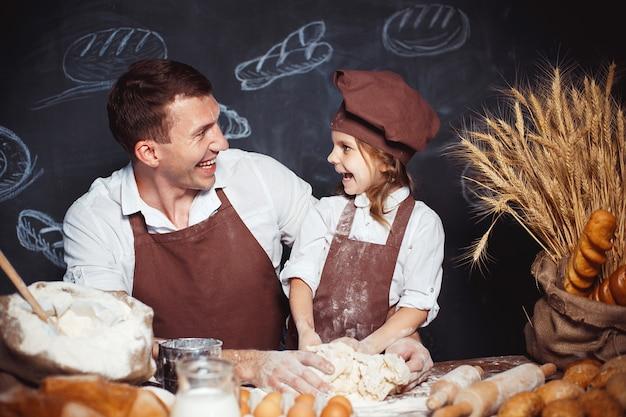 Roześmiany mężczyzna z córką robi chlebowi