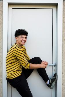 Roześmiany nastolatek w jaskrawej koszulowej pozyci w drzwi