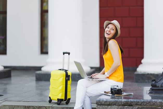 Roześmiany podróżnik turysta kobieta w ubraniach casual, kapelusz z walizką siedzi przy użyciu pracy na komputerze typu laptop pc w mieście na świeżym powietrzu. dziewczyna wyjeżdża za granicę na weekendowy wypad. styl życia podróży turystycznej.