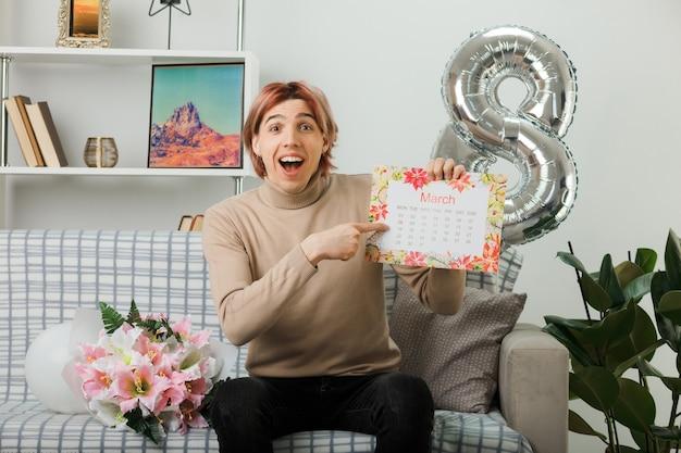 Roześmiany przystojny facet na szczęśliwy dzień kobiet trzyma i wskazuje kalendarz siedzący na kanapie w salonie