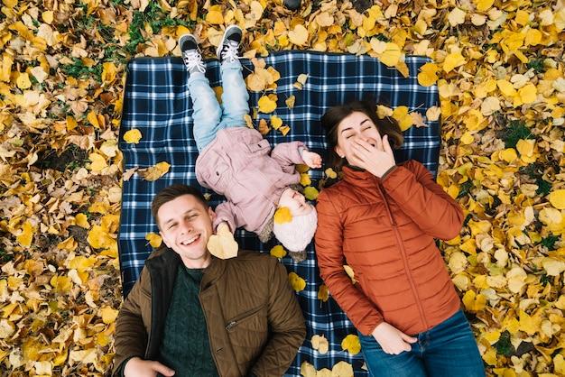 Roześmiany rodzinny lying on the beach na jesieni ziemi z żółtymi liśćmi