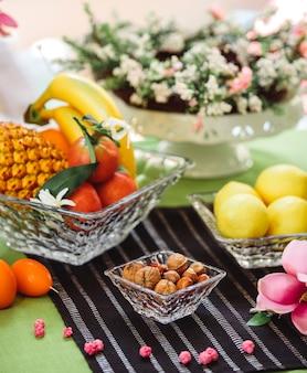 Rozeta z boku z orzechami w skorupce i miską owoców i cytryn na stole