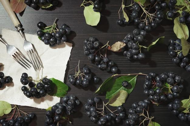 Rozgałęzia się czarne jagody aronii (aronia melanocarpa) na ciemnym stole