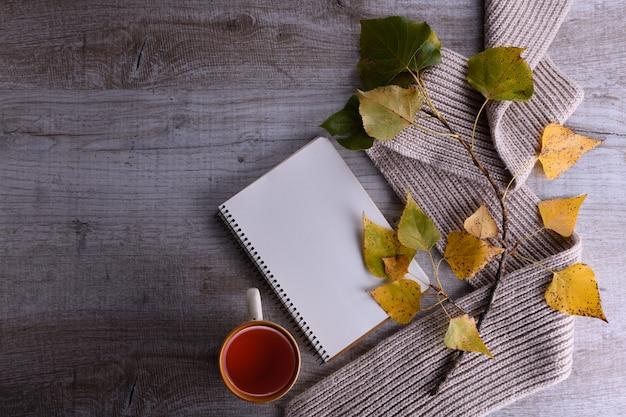 Rozgałęzia się z jesieni żółtymi i zielonymi liśćmi z szalikiem, notatnikiem i herbatą na lekkim drewnianym tle. jesienna kompozycja
