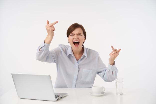 Rozgniewana młoda, krótkowłosa brunetka kobieta w niebieskiej koszuli pokazuje środkowy palec i wrzeszczy szaleńczo, marszcząc brwi ze złością na twarzy, pozując na biało