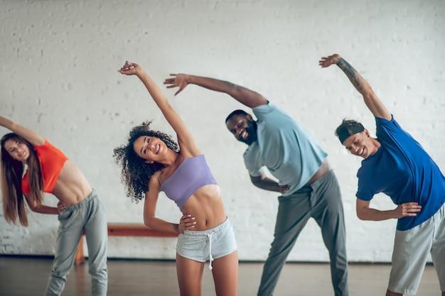 Rozgrzać się. grupa uśmiechniętych, energicznych młodych ludzi robiących synchronicznie przechylanie się na bok wyciągając rękę