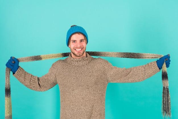 Rozgrzej chłodne dni przytulnym szalikiem. szczęśliwy człowiek nosi długi szalik. przystojny facet uśmiech z szalikiem w ręce. modny dodatek na zimę. stylowy szal z dzianiny w paski.