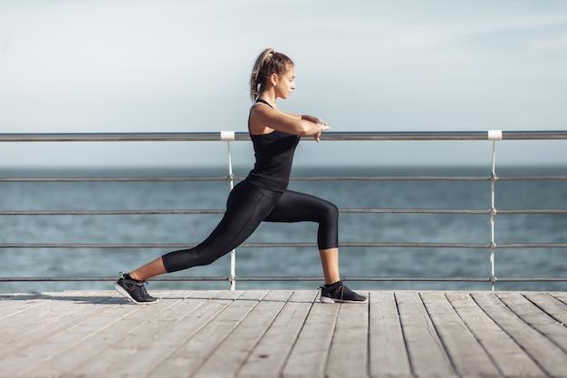 Rozgrzej się przed treningiem. szczupła młoda kobieta robi aerobik z doskonałym ciałem