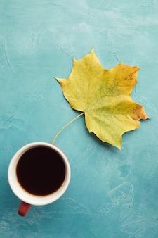 Rozgrzej się przy czarnej kawie jesienią. liść klonu na niebieskiej ścianie