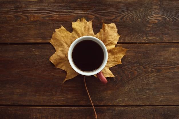Rozgrzej się przy czarnej kawie jesienią. liść klonu na rustykalnej drewnianej ścianie