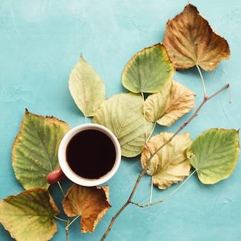 Rozgrzej się przy czarnej kawie jesienią. spadek liści na niebieskiej ścianie