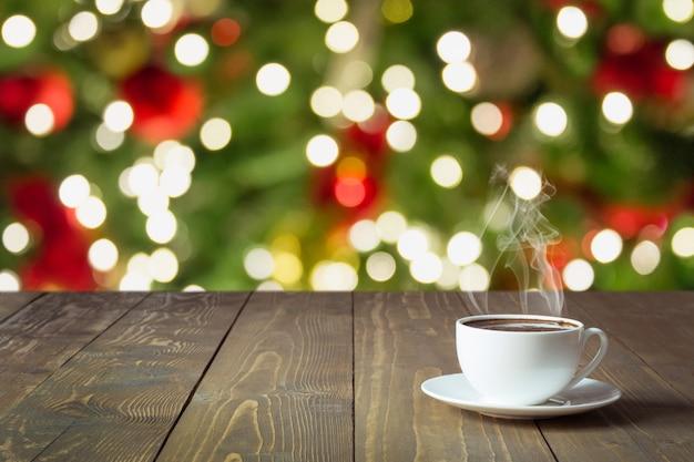 Rozgrzewająca filiżanka czarnej kawy na drewnianym blacie. zamazana choinka jako tło. czas świąt.