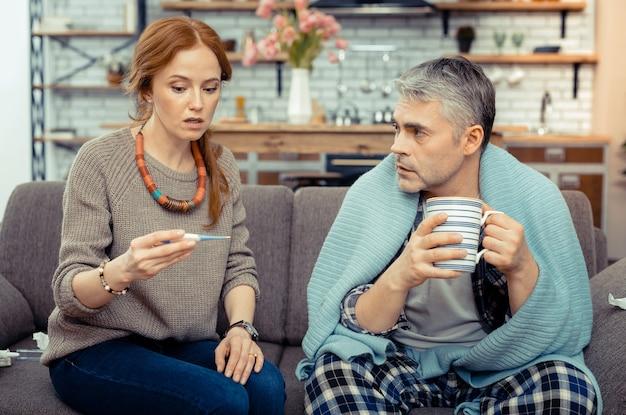 Rozgrzewający napój. miły chory mężczyzna siedzący z filiżanką herbaty podczas rozmowy z żoną