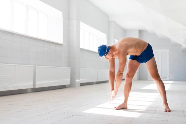 Rozgrzewający się mężczyzna przed pływaniem