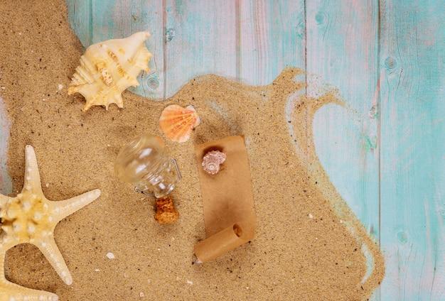 Rozgwiazda z seashells na dennym piasku na błękitnej drewnianej powierzchni
