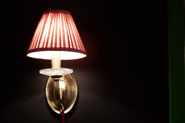 Rozjarzona jaskrawa lampa na ciemnej ścianie. skopiuj miejsce.