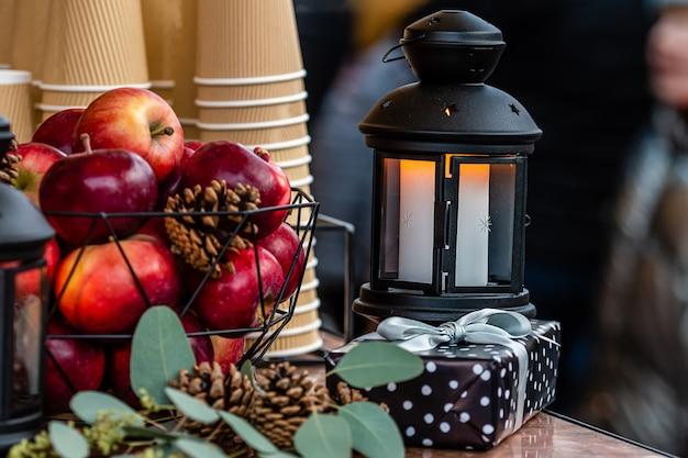 Rozjarzony świeczka lampion i kosz jabłka na stole w bożych narodzeniach wprowadzać na rynek w ryskim, latvia