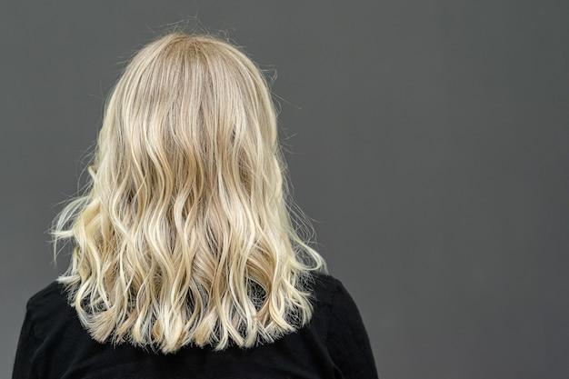 Rozjaśnianie włosów techniką shatush. blond kręcona fryzura od tyłu. miejsce na tekst
