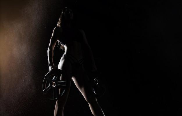 Rozkoszna atletka pozuje w studio z ciężarkami w dłoniach