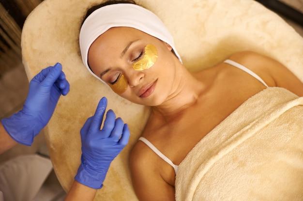 Rozkoszna latynoska kobieta ze złotymi hydrożelowymi łatami pod oczami relaksująca się w centrum spa