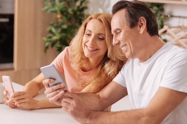 Rozkoszna, zgrana para dojrzała korzystająca z wolnego czasu w domu, uśmiechnięta, korzystająca ze smartfonów i dzieląca się szczęściem
