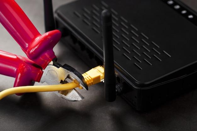 Rozłączenie połączenia internetowego, odcięcie żółtego kabla ethernet przecinakami do przewodów z czerwoną rączką na routerze wi-fi.