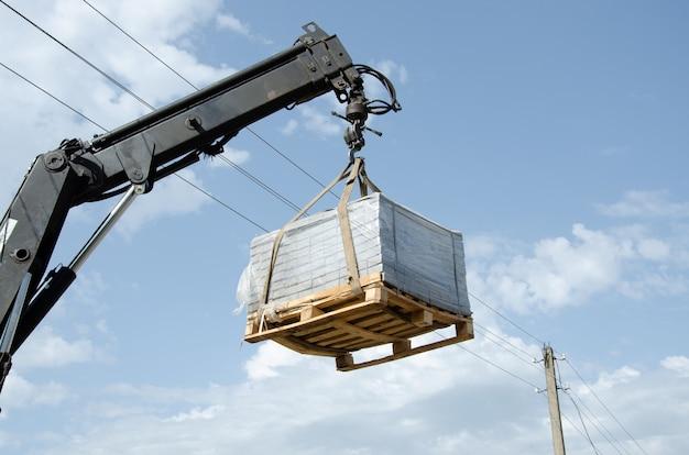 Rozładunek płyt chodnikowych z ciężarówki. mężczyźni rozładowują płyty chodnikowe za pomocą manipulatora. pracownicy rozładowują materiały budowlane z dużej maszyny.