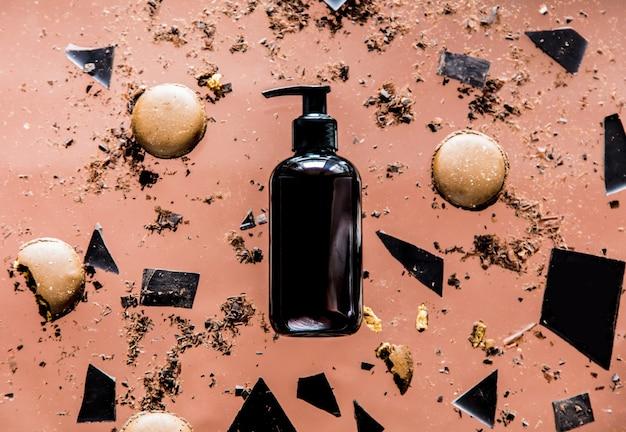 Rozlana czekolada z butelki, makaroniki i okruchy na różowej powierzchni. powyżej widok