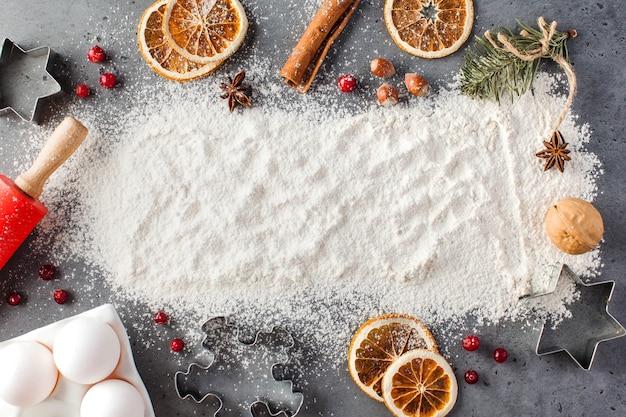 Rozlana mąka na szarej powierzchni otoczona wałkiem do ciasta, przyprawy