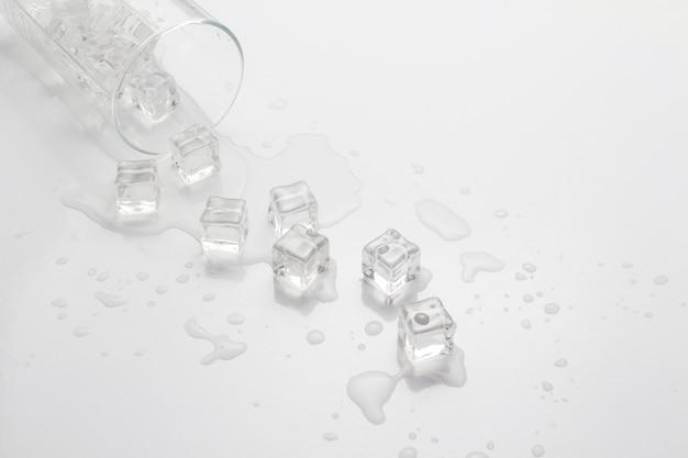 Rozlana szklanka wody z lodem na świetle