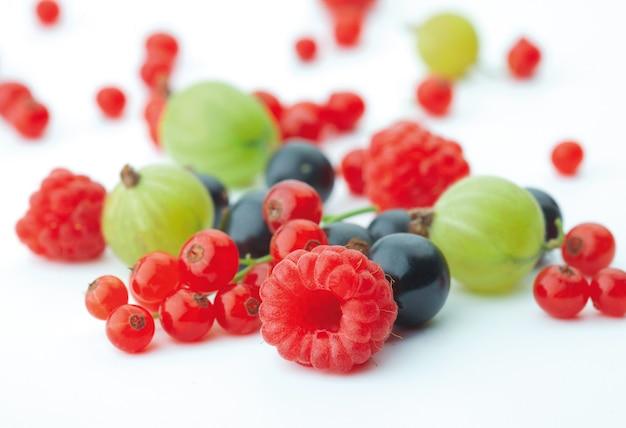 Rozlane jagody mieszane na białym tle whith maliny na pierwszym planie w centrum uwagi.