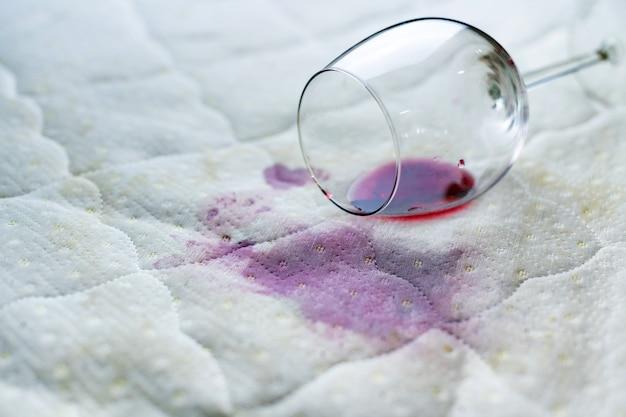 Rozlane kieliszek do wina na łóżku. przypadkowo upuszczony kieliszek na białym prześcieradle