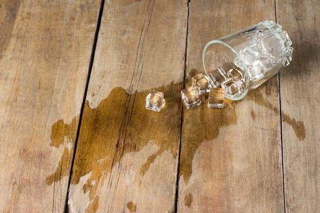 Rozlany napój z lodem, szkło na drewnianym tle.
