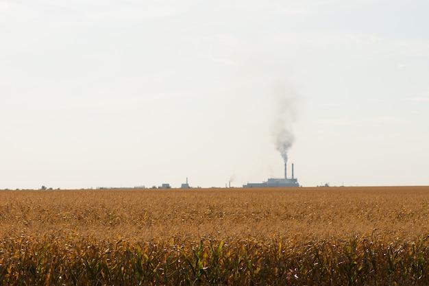 Rozległy widok brązowego pola z dymem z fabryki z daleka na jaśniejsze niebieskie niebo szare tło.