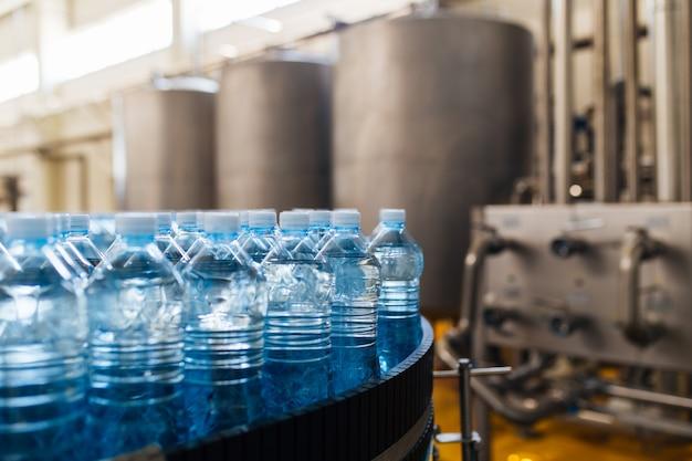 Rozlewnia - linia do butelkowania wody do przetwarzania i rozlewania czystej wody źródlanej do niebieskich butelek. selektywne skupienie.