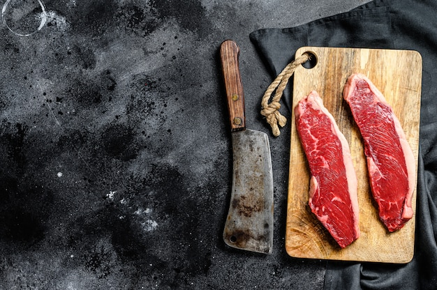 Rozłóż stek ze schabu na desce do krojenia. organiczne mięso wołowe. widok z góry
