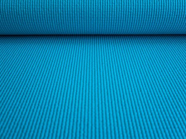 Rozłożona mata do ćwiczeń, pilatesu lub jogi. niebieska mata do treningu sportowego