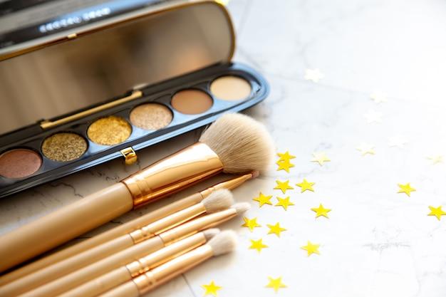 Rozłożona na płasko kompozycja dekoracyjnego kosmetyku składającego się z palety cieni i różnej wielkości pędzla do makijażu.