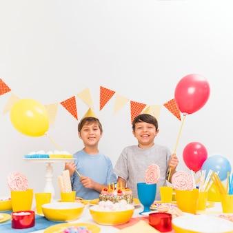 Rozmaitość jedzenie na stole z dwa chłopiec trzyma balony w przyjęciu