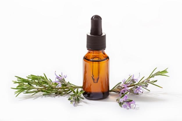 Rozmarynowy istotny olej w szklanej butelce odizolowywającej na bielu. olejek szałwiowy rosmarinus