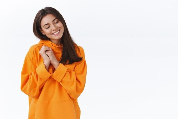 Rozmarzona i szczęśliwa delikatna młoda brunetka w pomarańczowej bluzie z kapturem pamięta coś miłego, zamknij oczy i uśmiechnij się wesoło, jak pamiętam niesamowitą letnią wycieczkę, zachwycona stojąca biała ściana