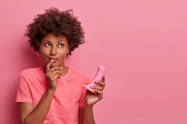 Rozmarzona kobieta wyobraża sobie, jak używa silikonowego dildo, chce osiągnąć orgazm z symulacji łechtaczki lub pochwy poprzez głęboką penetrację. sztuczne fallisy mogą wśliznąć się do kanału pochwy